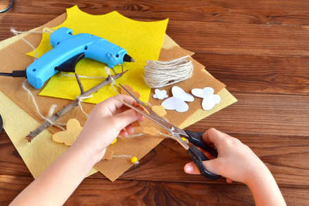 Child holds the scissors and cut out the felt flower. Scissors, hot glue gun, sheets of felt, decorative pendant with felt butterflies and flowers. Tree branch crafts for kids diy. Cheap home crafts