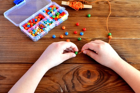 Children hands holding beads and cord. Baby sensory game