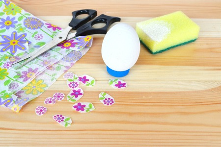 Easter egg, glue, scissors, napkins with a floral pattern on a natural wooden background