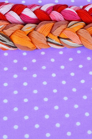 Embroidery threads of different colors on a purple background