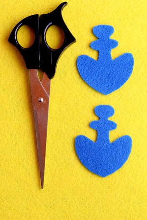 Two parts in the shape of an anchor cut from blue felt. The scissors on the yellow wool background. Lesson sewing fabric toy for children. Step. Closeup. Top view