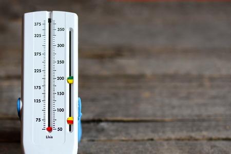Medidor de flujo máximo aislado sobre fondo de madera. Dispositivo médico de mano utilizado para controlar el aliento de una persona que sufre de asma bronquial. Medidor de flujo máximo de amplio rango de valores. De cerca