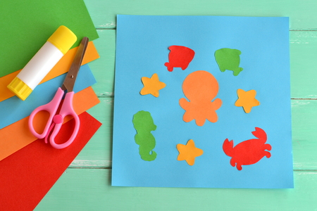Paper applique with sea animals and fishes. Art lesson in kindergarten. Paper sea animals - octopus, fish, starfish, seahorse, crab. Kids crafts. Sheets of colored paper, scissors, glue