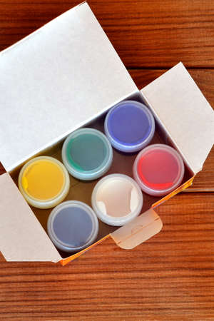 Jars with gouache on brown wooden background. A set of colored paint