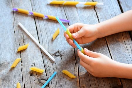 子供のための細かい運動能力の開発。小さな子供は、彼の手でストローと生パスタを保持します。創造的な子供の活動。手と目の調整を改善するた 写真素材
