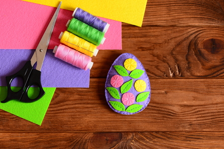 Felt Easter egg decor, scissors, thread group, needle, colored felt sheets on wooden background with copy space. Embellished felt Easter egg decorating idea. Simple and beautiful Easter gift. Top view