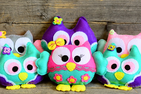Nice kids felt toys. Colored stuffed owls toys on vintage wooden background. Decorations crafts made of felt. Fun kids background. Closeup Stock Photo - 70701259