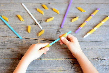 learning by doing: Small child holds straw and dried tube pasta in his hands. Child stringing pasta onto straw. Simple task for development of fine motor skills in children