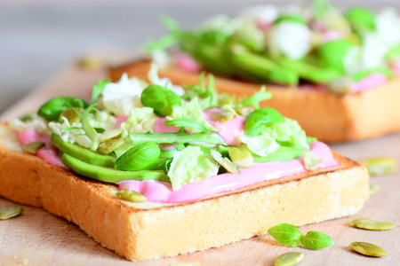 Vegetarian avocado sandwich recipe idea. Homemade sandwiches cooked with sliced ??avocado, fresh lettuce, basil and pumpkin seeds. Healthy eating lifestyle. Closeup Stock Photo