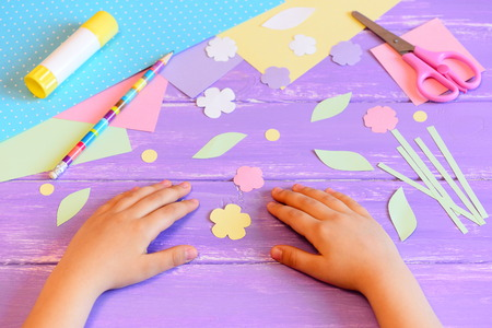 Small child makes a greeting card for mother. Colored paper, templates, flowers and leaves cut from paper, scissors, glue stick, pencil on a wooden table. Childrens crafts for mothers day or March 8 Stock Photo