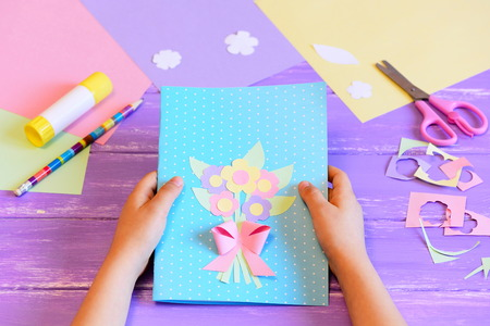 Small child made a greeting card with flowers for mom. Child holds a card in his hands. Tools and materials for children's art creativity on table. Mother's day or March 8 greeting card DIY idea