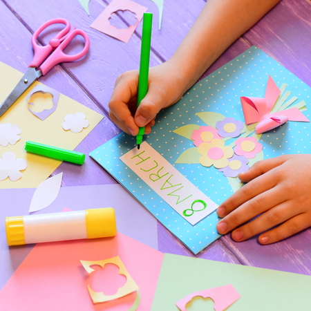 Creating a greeting card with flowers for mom. Child holds a pen in hand and writes March 8. Tools and materials for children's art activity. March 8 greeting card crafts concept