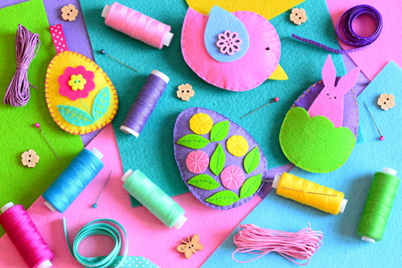 Felt Easter eggs with flowers and bunny, a felt bird. Easter ornaments set, colored thread spools, felt sheets, pins, ribbons, wooden buttons on a table. Colorful Easter background. Top view. Closeup 版權商用圖片