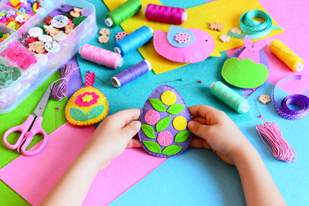 sewing box: Child made a felt Easter egg ornament. Small child holds a felt Easter egg ornament in his hands. Easter crafts, craft tools and materials on a table. Festive spring crafts concept Stock Photo