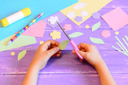 Small child creates a greeting card for mom. Step. Child holds scissors in his hands and cuts a leaf from paper. Materials for paper crafts on a table. Mother's day, birthday, March 8 easy crafts