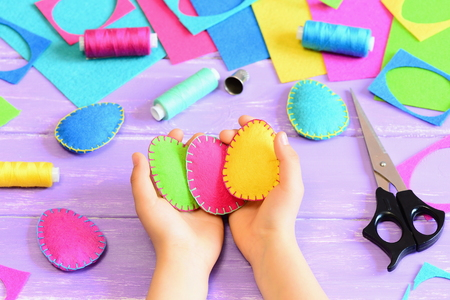 table scraps: Child holding a felt Easter eggs in his hands. Little child made Easter crafts of felt. Tools and materials for needlework on wooden table. Simple kids crafts concept