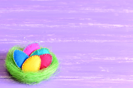 Easter eggs in a nest. Felt Easter eggs set in a green sisal nest isolated on purple wooden background with copyspace for text. Bright festive background