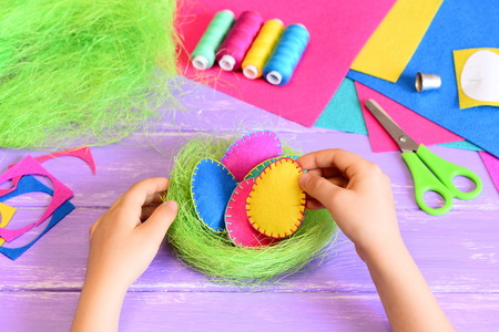 Little child does Easter decor. Child holds a felt egg in hand. Colourful felt Easter eggs and sisal nest, handicraft tools and materials on a table. Easy and attractive Easter decor idea