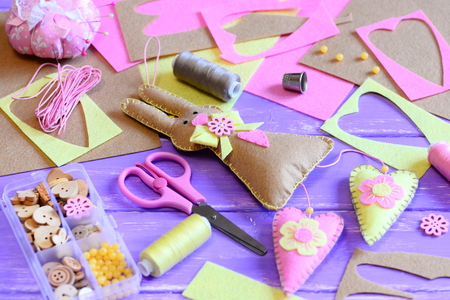Felt Easter bunny with hearts decor. Easter wall decor idea. Scissors, pincushion, pins, thread spools set, thimble, buttons and beads in a box, felt sheets on a wooden table. Easter crafts background