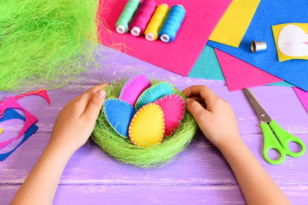 Small child made Easter decoration. Child holds beautiful felt Easter eggs and sisal nest decoration in his hands. Craft tools and materials on a table. Easy handmade Easter gift idea for kids Stock Photo