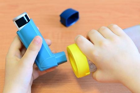 Niño pequeño que sostiene el inhalador y el espaciador del asma en sus manos. El espaciador del asma y el inhalador de aerosol para el tratamiento y el control del asma bronquial, la alergia. Cómo usar un inhalador con un espaciador