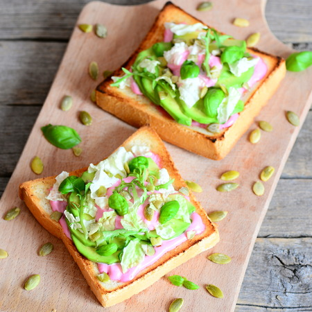 Open sandwiches with avocado, lettuce, basil, pumpkin seeds and creamy pink beet sauce. Simple and healthy vegan sandwiches on a wooden board. Closeup