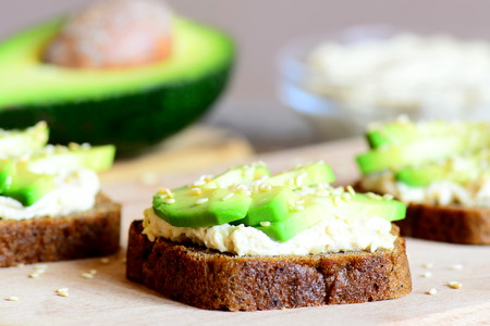 Vegetarian avocado and hummus sandwiches on a wooden board. Simple and healthy open sandwiches. Healthy food lifestyle. Meatless menu. Closeup Stock Photo