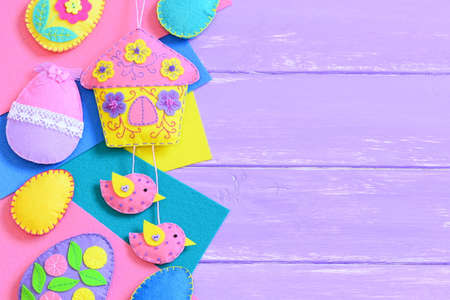 Fun Easter background. Homemade vibrant felt Easter crafts on lilac wooden background with empty copy space for text. Felt house with birds decoration, felt eggs decorations set. Top view 版權商用圖片