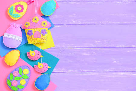 Children Easter background. Handmade vibrant felt Easter crafts on lilac wooden background with empty copy space for text. Felt house ornament, felt eggs ornaments set. Top view 版權商用圖片