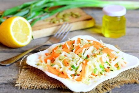 Healthy vegetable salad on a plate. Salad with fresh cabbage, carrots, green onions and pumpkin seeds. Fork, lemon half, olive oil in a jar, green onions on vintage wooden table. Healthy eating 版權商用圖片