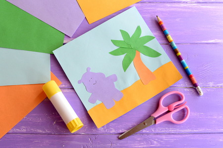 Summer paper card, scissors, glue stick, colored paper sheets on lilac wooden background. Hippo and palm tree preschool craft. Animals crafts arts project idea for kids
