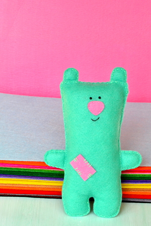 Cute green felt Teddy bear - handmade children toy Stock Photo