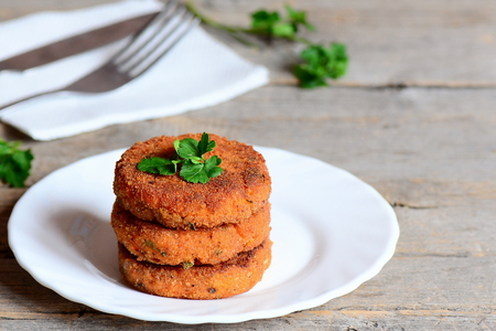 comfort food: Home carrot cutlets on a plate and on a wooden table. Healthy fried carrot cutlets with green onions and parsley. Simple and quick vegetable cutlets recipe