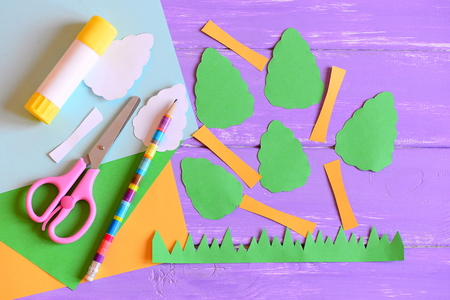 Creating Earth day card. Step. Tutorial. Trees and grass cut from colored paper, scissors, glue stick, pencil, template, paper sheets on a wooden table. Earth day paper crafts idea for kids. Top view