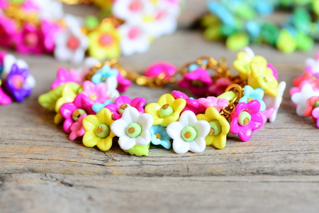 Set of bright bracelets on old wooden background. Bracelets made of colorful plastic flowers, leaves and beads. Accessories for a small girl. Closeup