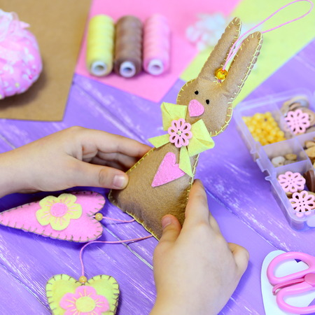 paper hanger: Little girl holds a felt Easter bunny toy in hands. Girl shows a felt bunny with hearts. Handmade Easter gift. Tools and materials for kids creativity on a wood table. Fun crafts project for children