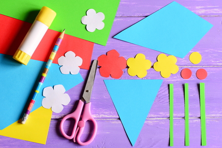 Creating paper crafts for mother's day or birthday. Step. Cut details to making a paper bouquet for mom. Scissors, glue stick, flowers templates, pencil on a table. Children's creativity. Top view