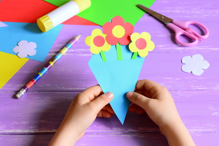 Little child made paper crafts for mother's day or birthday. Child holds a paper bouquet in hands. Easy and beautiful gift for mom. Scissors, glue stick, flowers templates, pencil on a wooden table