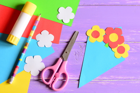 Creating paper crafts for mothers day or birthday. Step. Tutorial. Paper bouquet gift for mommy. Scissors, glue stick, flowers templates, pencil on a table. Easy kids crafts idea. Top view