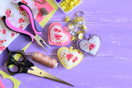 Beautiful hearts keyring. Hand felt and fabric keyring or bag charm. Organizer with plastic flowers, scissors, pliers, felt, needle, thread, scrap. Set for home craft. Wood background with copy space