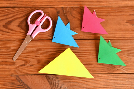 aquarium hobby: Paper sheets, scissors on a brown wooden table. How to make origami fish