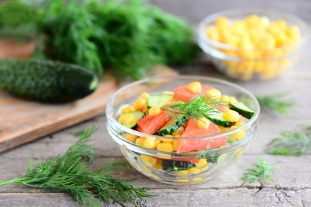 Cucumbers, tomatoes and corn salad. Bright, colorful and yummy salad in a bowl and on a wooden table. Healthy diet vegetable salad photo. Rustic stile Stock Photo