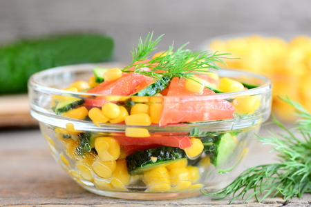 flavorful: Fresh cucumbers, tomatoes, corn and dill salad. Bright, natural and flavorful salad in a bowl. Homemade fresh vegetable salad recipe. Closeup