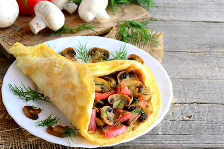Mushrooms omelette with tomatoes. Homemade omelette with fried mushrooms, fresh tomatoes slices and finely chopped dill on a plate and on a wooden table. Fast and easy stuffed omelette. Rustic style Reklamní fotografie