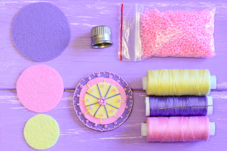 Felt flower, colored felt circles, thread spools, needle, thimble, pink beads on a wooden table. Sewing felt flower tutorial. Simple round felt flower crafts for kids. Top view Stock Photo