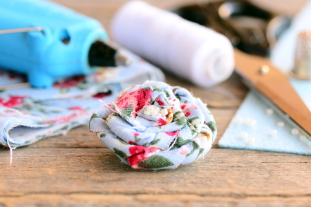 Beautiful flower brooch. Fabric textile eco friendly brooch decorated with beads, hot glue gun, scissors, thread spool, thimble, felt on old wooden table. Summer flower brooch crafts. Craft concept