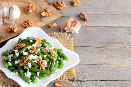 Green string beans with cottage cheese and walnuts on a white plate and vintage wood background with copy space for text. Green beans photo. Green string bean recipe. Green beans warm salad
