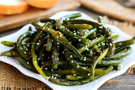 Fried garlic arrows appetizer. Spicy green garlic arrows with spices and sesame seeds on a plate. Easy, cheap and healthy recipe idea. Closeup Stock Photo