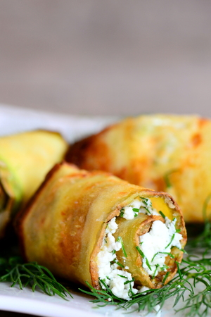 Rolls made from zucchini strips and stuffed with cottage cheese and dill. Fried zucchini rolls garnished with dill on a plate. Home beautiful appetizer recipe. Vertical photo