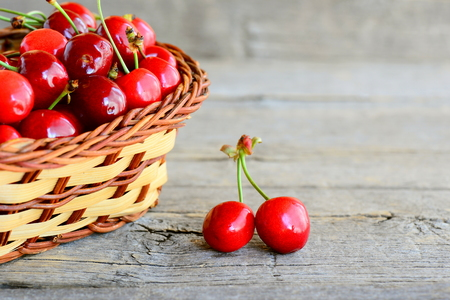 Two juicy sweet cherries, wicker basket with sweet cherries on an old wooden table. Summer natural fruit food Stock Photo